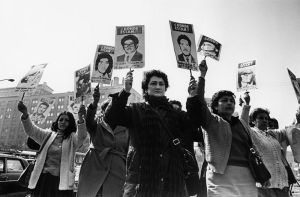 Women of the Association of Missing Relatives demonstrate outside the government palace during the military regime of Pinochet By Desconocido [CC-BY-SA-3.0-2.5-2.0-1.0 (http://creativecommons.org/licenses/by-sa/3.0) or GFDL (http://www.gnu.org/copyleft/fdl.html)], via Wikimedia Commons